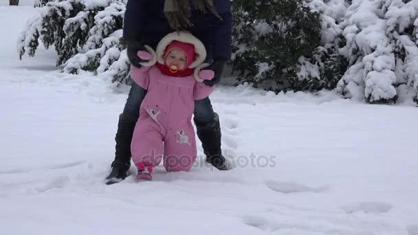 Piccolo del bambino di imparare a camminare. Donna con la sua ragazza del bambino in winter park. 4k