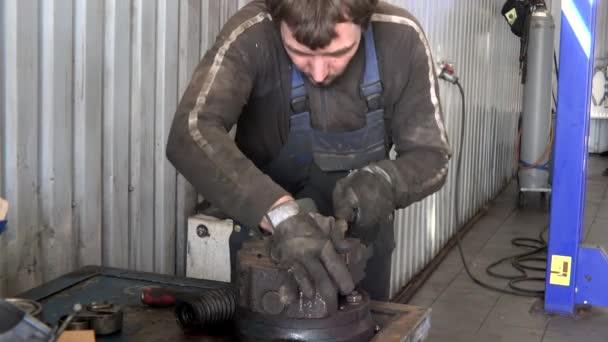 mechanik chlap grind rezavý kov nástrojem rašple v garáži
