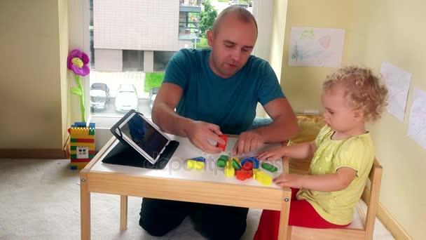 Capricious child dont want play with bricks and father give daughter tablet