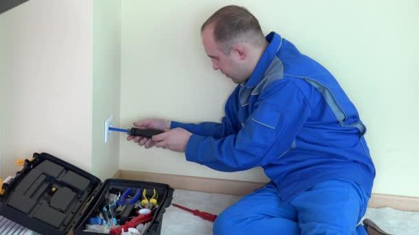 Muže naštvaný elektrikář s indikátorem zkušební napětí na elektrické zásuvky