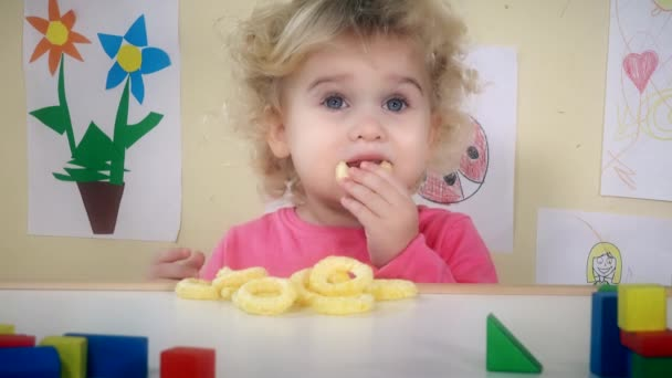 little girl eating corn circle sitting near her table toys and drawings