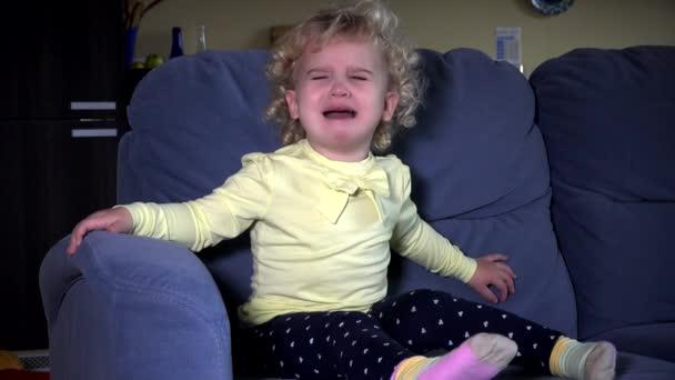 Ha sottolineato carina piccola ragazza gridante si siede sul sofà