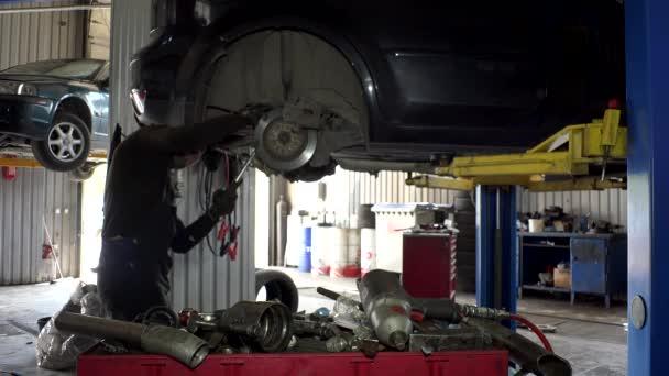 auto mechanik chlap použít různé nástroje k opravě brzdový systém vozu v garáži.