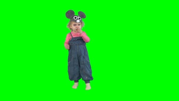 Niedliche kleine Mädchen mit Maus Hut Essen süß ringförmigen Roll isoliert auf grün