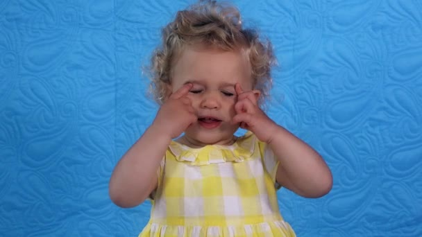 Little baby girl showing nose, eyes, ears, mouth, tongue with finger