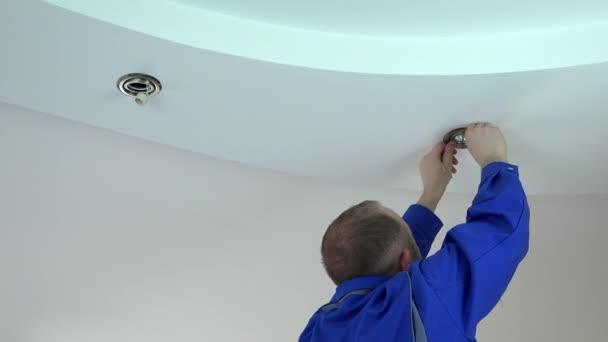 muž elektrikář nainstalovat nebo nahradit halogenové světlo do stropu