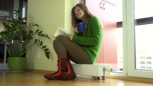 Heizkörper Zum Sitzen schöne frau mit teekanne und buch sitzen auf warmen heizkörper in