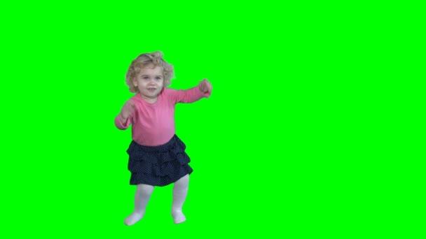 entzückendes Mädchen mit blonden lockigen Haaren tanzt und springt isoliert auf Grün