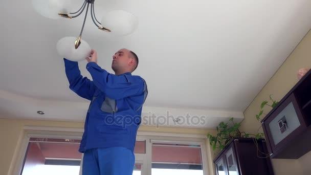 Hospodyně člověk vylézt nahoru a měnit žárovky v lustru