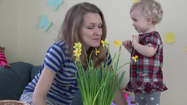 Mother and daughter look at houseplants and narcissus flowers.