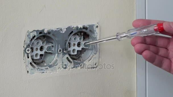 Mano di elettricista verifica tensione elettrica su una presa a spina.