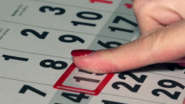 Business woman finger push red marker on calendar page