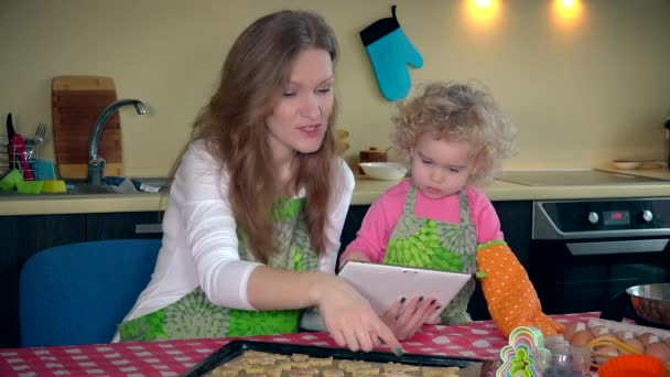 Matka a dítě připravuje pečivo při pohledu na kuchařku na tabletovém počítači