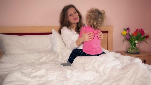 Mosolygó anya-anya és aranyos lány lány jó szórakozást az ágyban