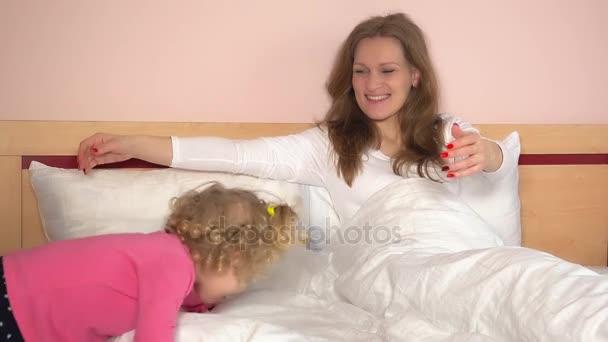 Csintalan kislány jött az ágyban, és ölelés az anyja. Szép családi lányok jó szórakozást