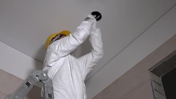 Kvalifikované konstruktor člověk dělat sádrokartonové stropní otvory pro světelná instalace