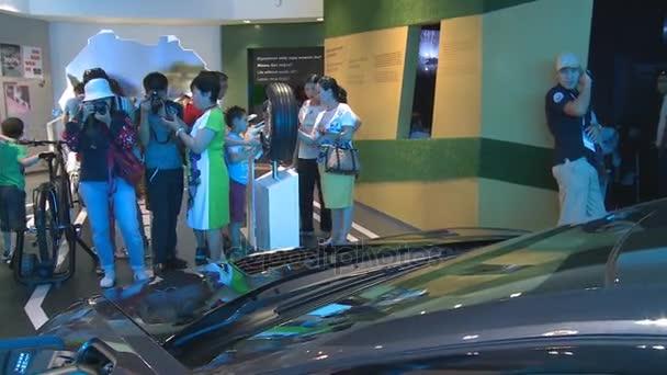 Návštěvníci lidí fotografujících nové hybridní auto v Německu pavilonu Expo 2017