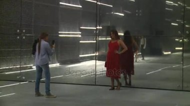 Kazakh woman in red posing for daughter on laser installation wall in Expo 2017