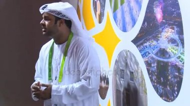 Male Arab guide in hijab showing Arab pavilion stand for businessman people