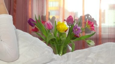 Bouquet of tulip flowers and happy girl talking with smart phone.
