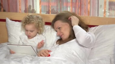 Mother and toddler daughter in bed with tablet computer