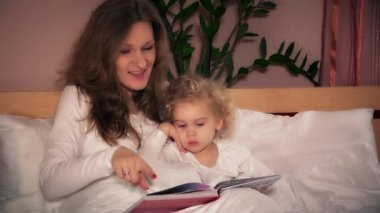 Pretty young mother reading book to her cute toddler daughter sitting in bed