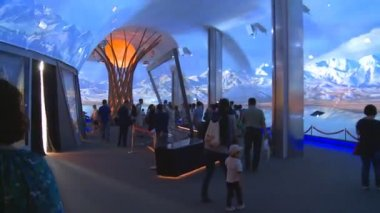 People visiting pavilion with modern tree and egg and mountain projections
