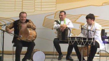 Caucasian charismatic drummers men play rhythm in Azerbaijan pavilion in EXPO