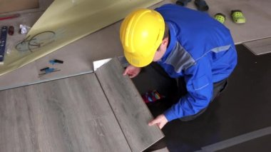 Male handyman lay wooden laminate boards on floor in new house room