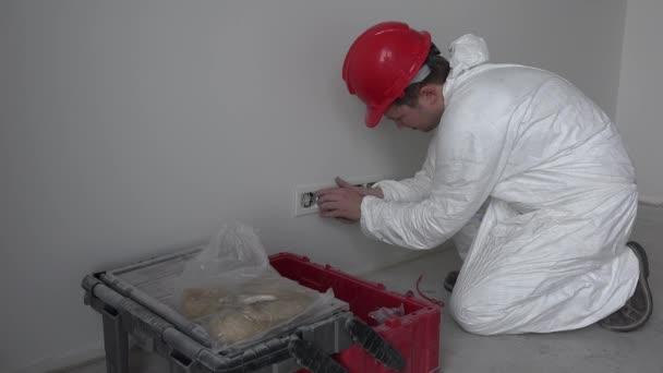 Kavkazská mužské elektrikář montážní zásuvka zásuvky stěnu v nové budově