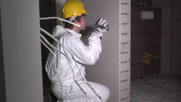 Operaio elettricista presso cavo e luce passare installazione presa presa a parete