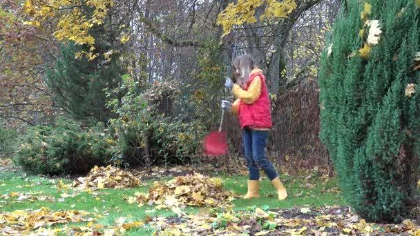 couple have fun raking autumnal leaves in garden. 4K