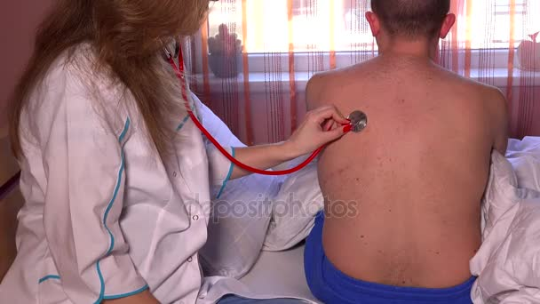 Closeup of female doctor using stethoscope to check breathing of patient