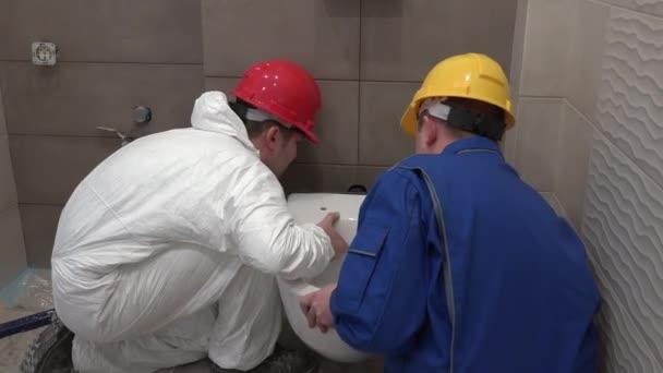Männer in arbeitskleidung hängende wc wc schüssel in neuen