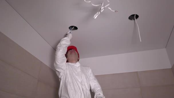 stavební dělník mužské vylézt na žebřík a řez díra do sádrokartonového podhledu