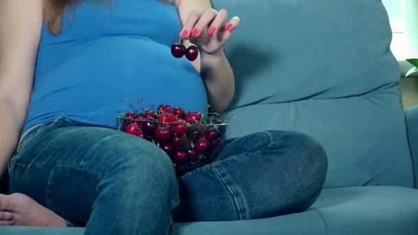 Těhotná žena ruce tahu velké břicho a mísa s Višňová na kolenou