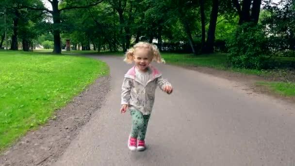 Lustiges blondes Mädchen mit Zöpfen läuft vor laufender Kamera durch Parkstraße