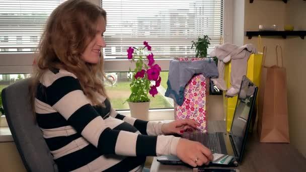 Happy těhotná žena platit za online nákup kreditní kartou