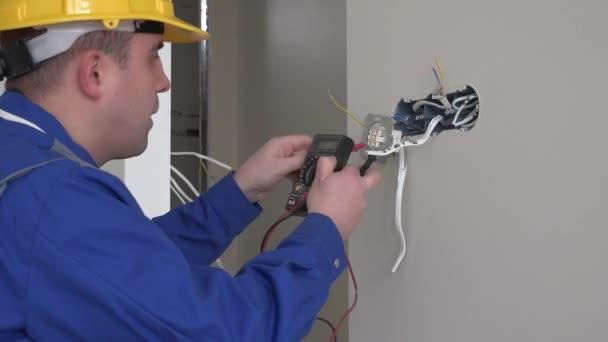 Profesionální elektrikář člověka pomocí speciálního nástroje pro kontrolu napětí zásuvky ve zdi