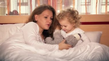 Sweet little girl and her beautiful young mom singing lullaby for toy bear
