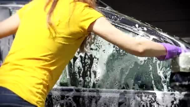 Žena pracovník mytí auta s houbou na mytí aut