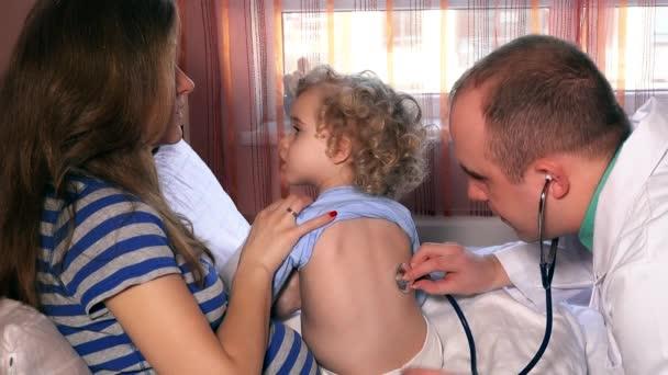 Matka drží dítě dcera pro vyšetření lékař pediatr s stetoskop