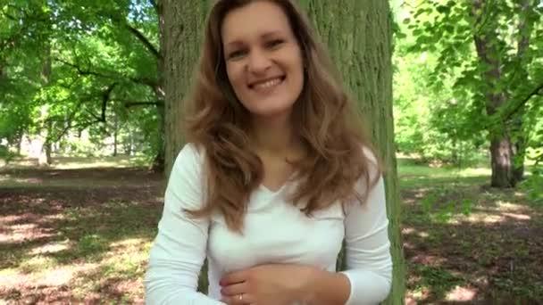 Usmívající se těhotná žena při pohledu na fotoaparát nabídka stoke její velké břicho