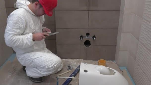 Qualifizierte klempner mann arbeitet auf wc schüssel hand berg in