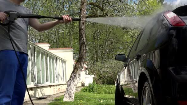 Profesionální služby muž s vysokotlakým vodním paprskem mytí auta