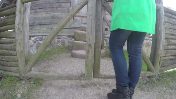 woman open wooden gate and climb on stone stairs. 4K