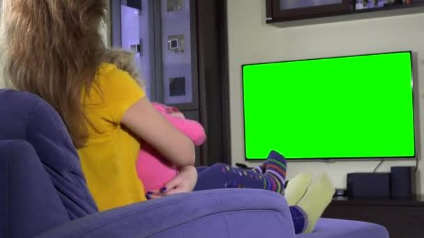 Šťastný matka s její roztomilý dcera dívka sleduje televizi vtipné karikatury na pohovce