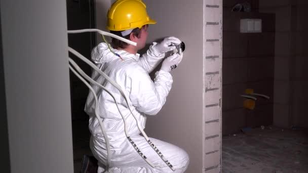 Soket vypínač montážní elektrikář. Pracovník muž s helmu a pracovní oblečení