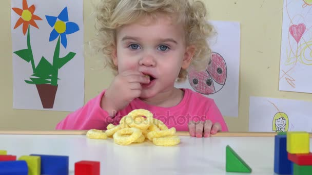 Cute face girl eating corn circle sitting near her table toys and drawings