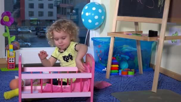 Sladká blondýnka batole dívka připravit hračka postel postýlka pro panenku baby doma